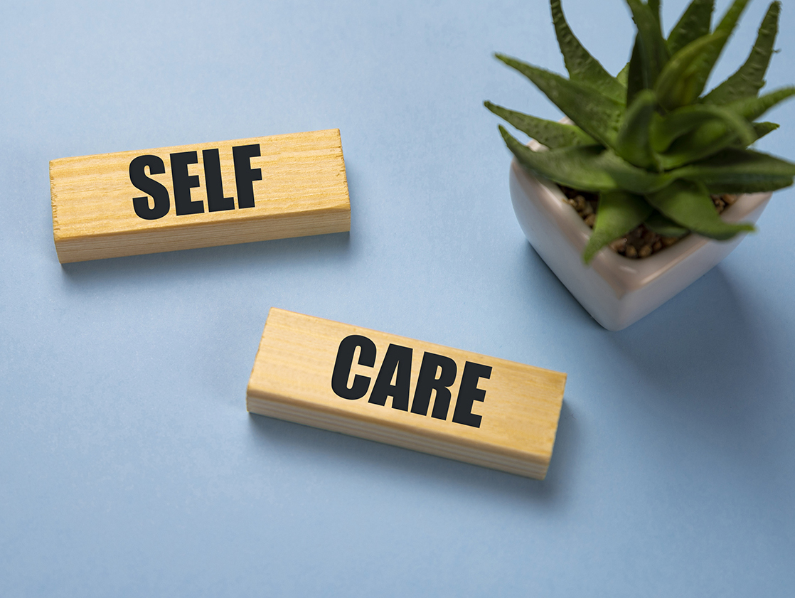 Self-care word on lightbox on blue background flat lay. Take care of yourself.
